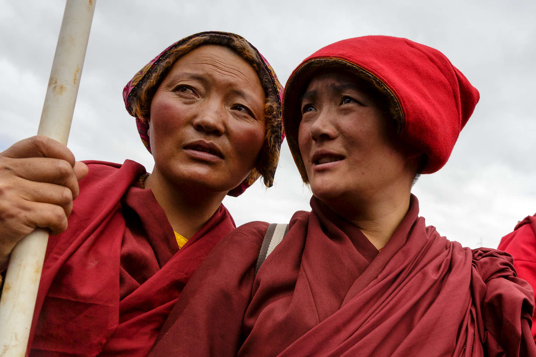 Two nuns watch on as 10,000 of their fellow devotees stream into the green hills surrounding Yarchen for a month of meditation before the onset of winter.