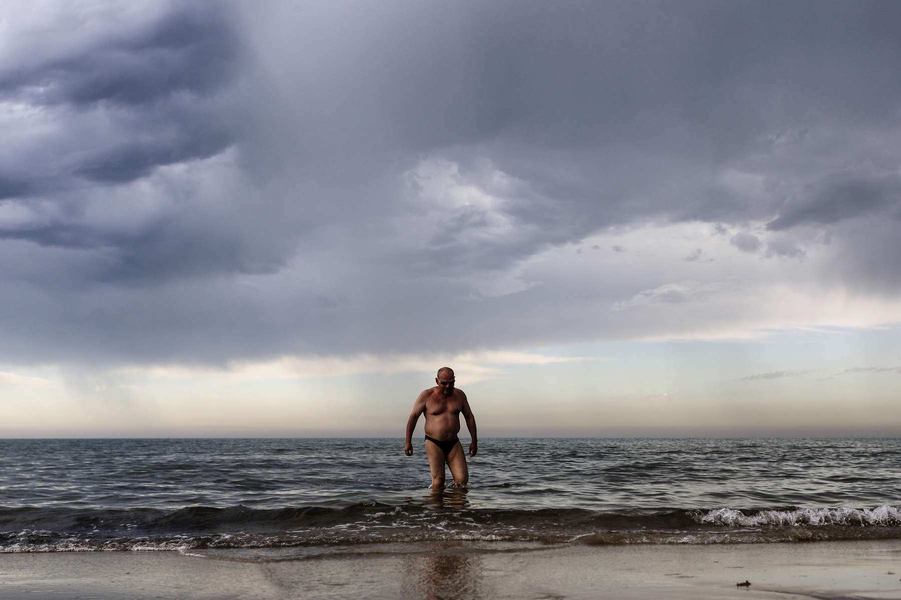 MELBOURNE, NEW SOUTH WALES - DECEMBER 24:  A man wades through the shallows at Mentone Beach as a summer storm rolls across the city. December 24, 2016 in Melbourne, Australia.  (Photo by Brook Mitchell/Fairfax Media)