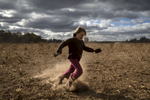 COONABARABRAN , NEW SOUTH WALES - JUNE 17:  Heidi Taylor, 7, kicks up dust on the family farm outside Coonabarabran. In the Central Western region of New South Wales, Australia, farmers continue to battle a crippling drought which many locals are calling the worst since 1902. In Warrumbungle Shire, where sharp peaks fall away to once fertile farmland the small town of Coonabarabran is running out of water. The town dam is down to just 23% capacity, forcing residents to live with level six water restrictions. The New South Wales State government recently approved an emergency drought relief package of A$600m, of which at least A$250m is allocated for low interest loans to assist eligible farm businesses to recover. The package has been welcomed, though in the words of a local farmer {quote}it barely touches the sides{quote}. Now with the real prospect of a dry El-Nino weather pattern hitting the state in Spring, the longer term outlook for rain here is dire. June 17, 2018 in Coonabarabran, Australia.  (Photo by Brook Mitchell/Getty Images)