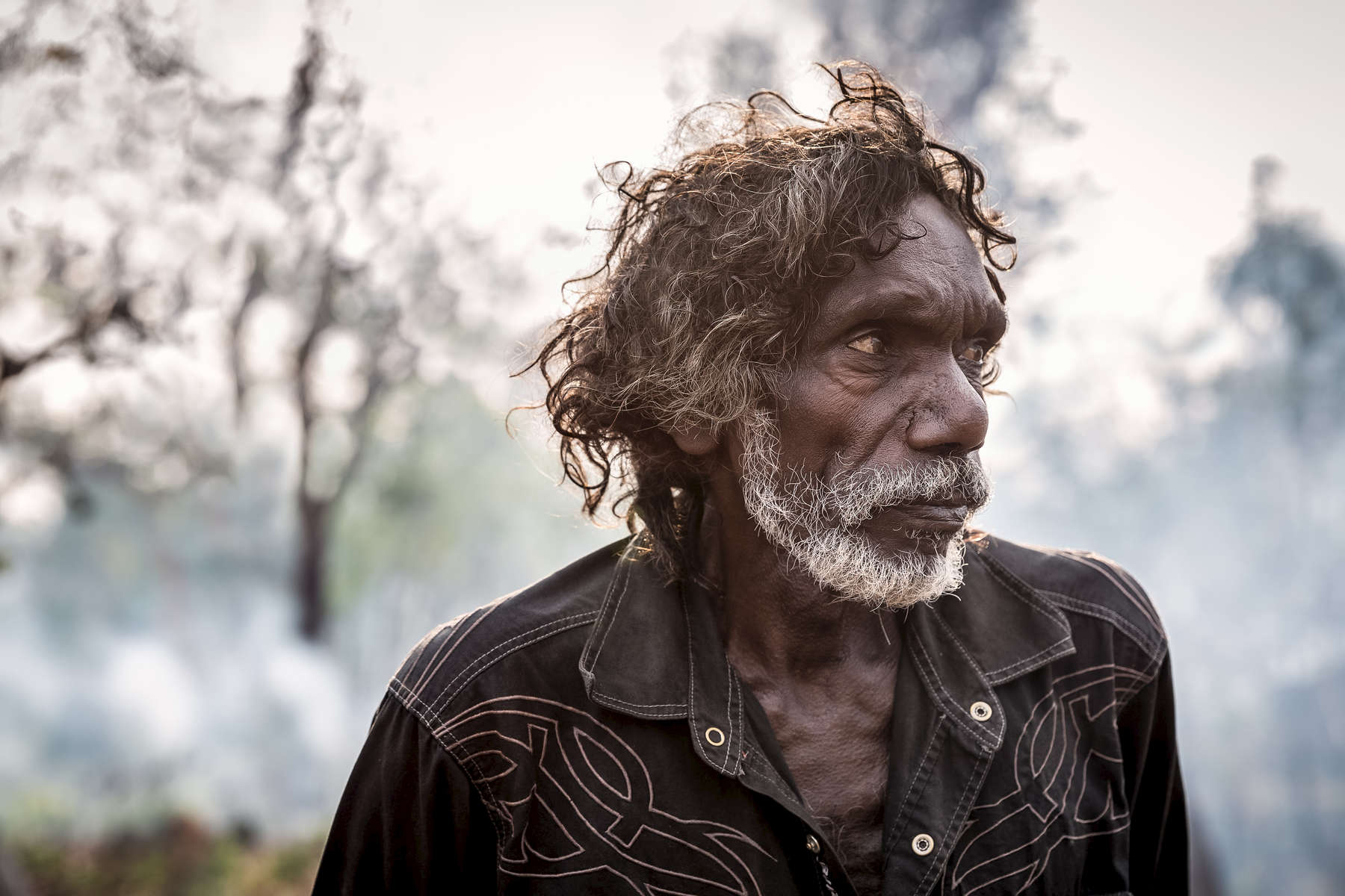 Tom Noytuna backlit by the afternoon sun and smoke from a fire started by the family the previous day in Benebenimbi, a remote part of central Arnhem Land.  Fires are lit here to manage the land, regenerating growth and keeping fuel for larger fires at low levels.