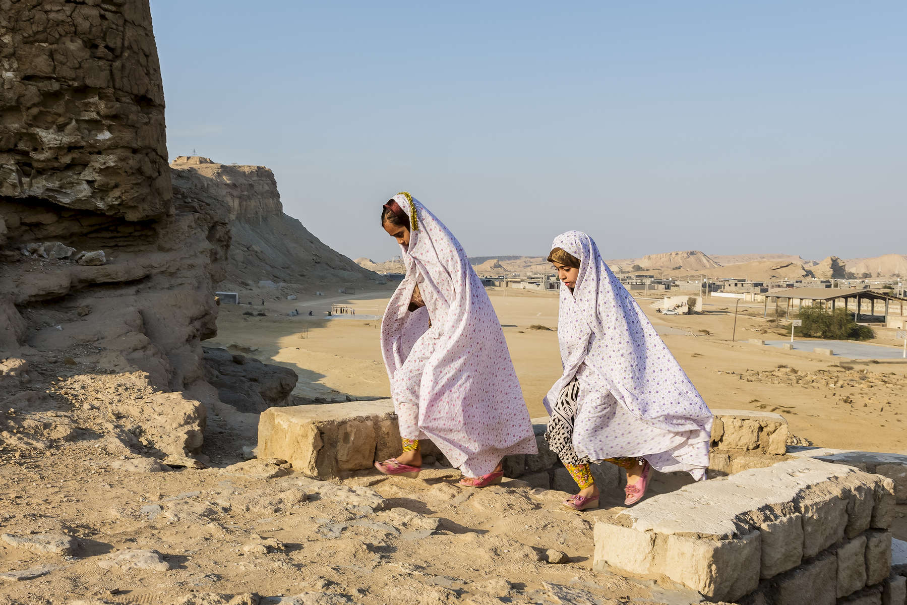 Two young girls pass the ruins of a Portuguese castle in the village of Laft, Qeshm Island, Persian Gulf.  In 2009 Iran and Portugal prepared joint plans to restore historical sites such as this, which are scattered around the gulf region.  Little work seems to have taken place.