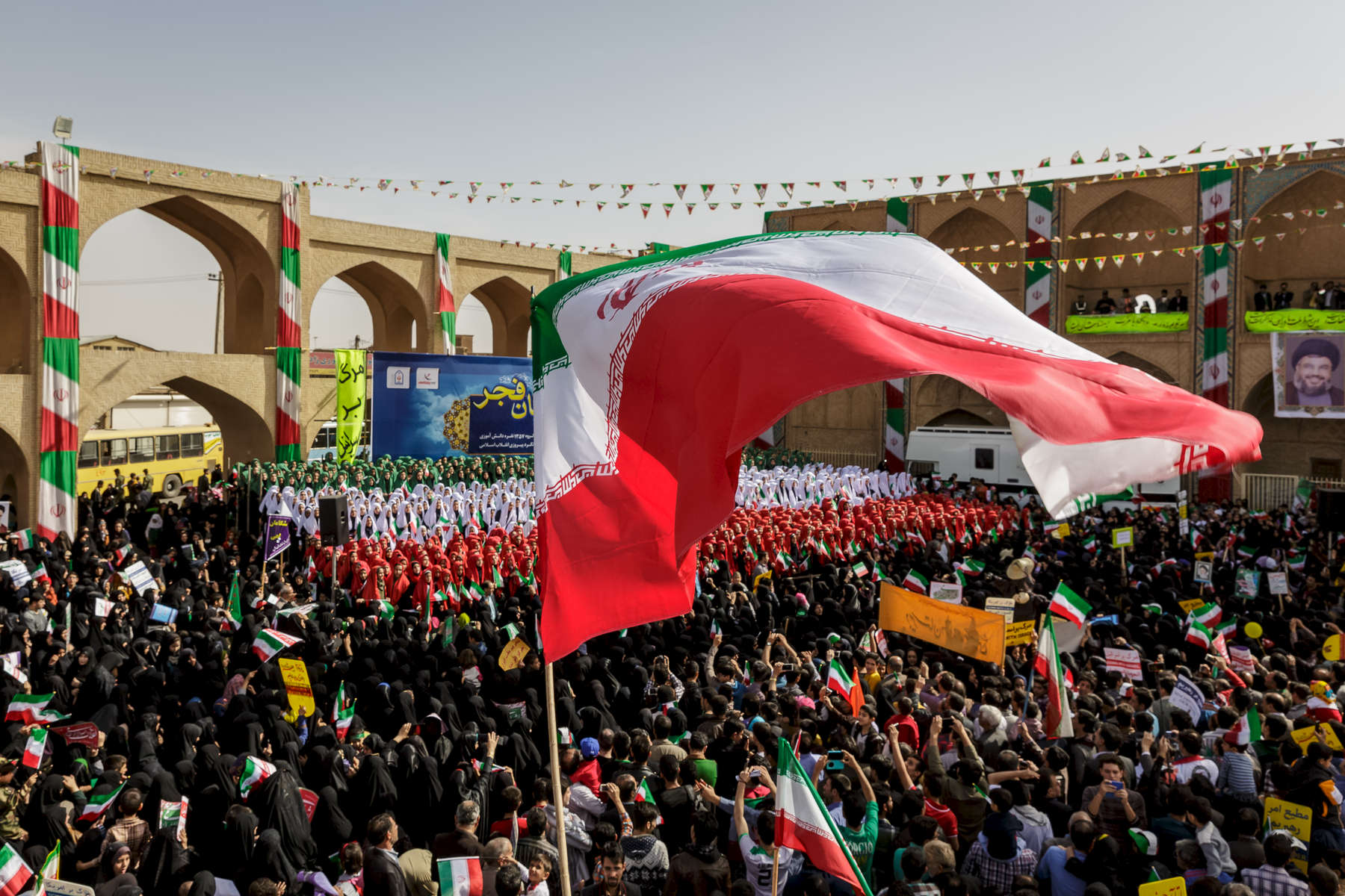 Large Iranian national flag being flown in the town centre of the city of Yazd on Febuary 11th rallies in remberance of the 1979 Islamic revoloution.  The photographer was briefly allowed onto a platform overlooking the crowd, which officals estimated at around 20,000 people, just a small percentage of the one million strong population of the city.