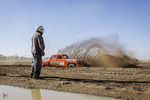 A bogged driver watches on as he is lapped by a fellow competitor. Photo: Brook Mitchell