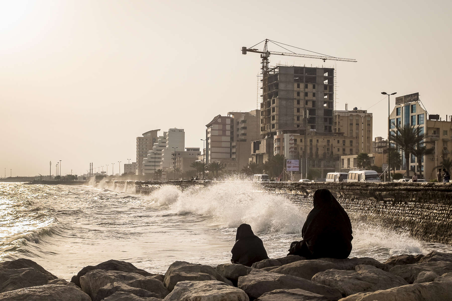 Women taking in the sunset view and high tide waves crashing into a breakwall, Bandar Abbas, Persian Gulf Coast, Iran.