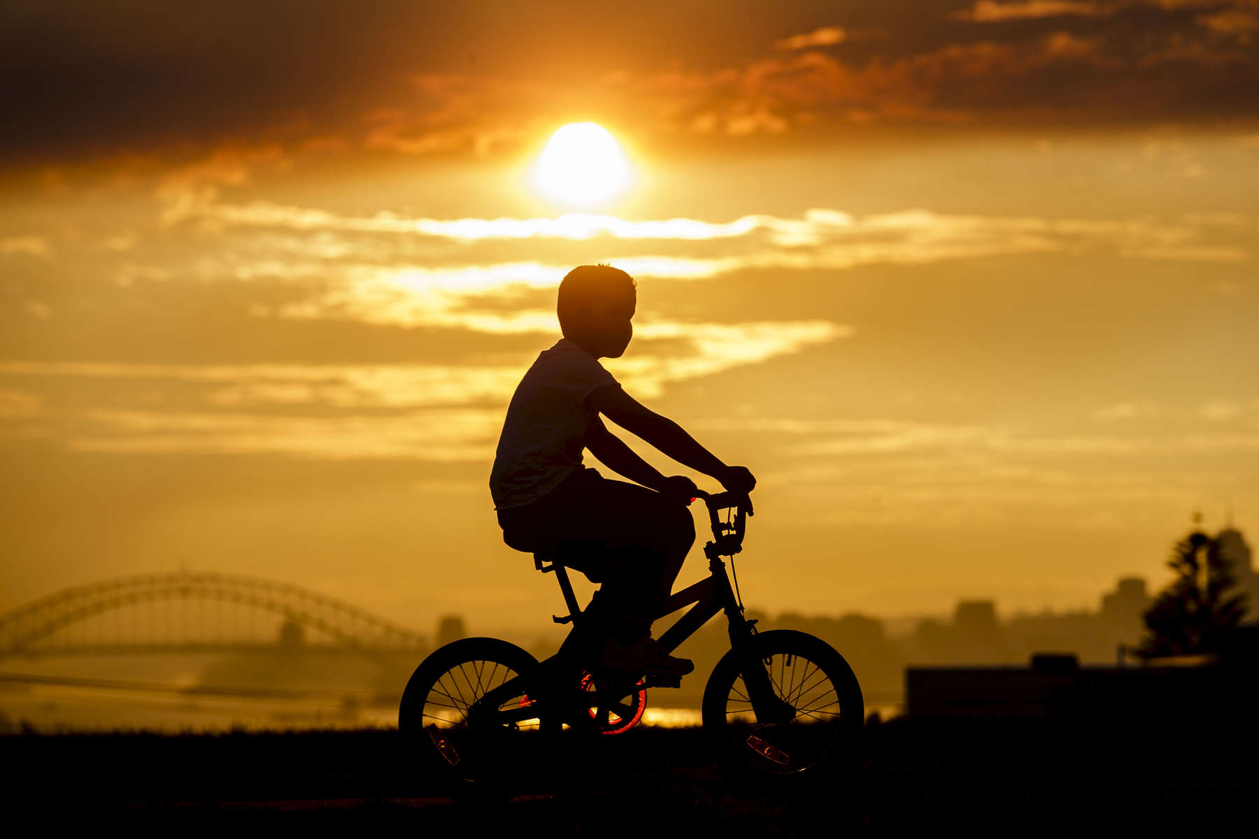 A young boy rides his bike in Dover Heights as heavy smoke haze blankets Sydney on 14 August, 2017. Photo: Brook Mitchell