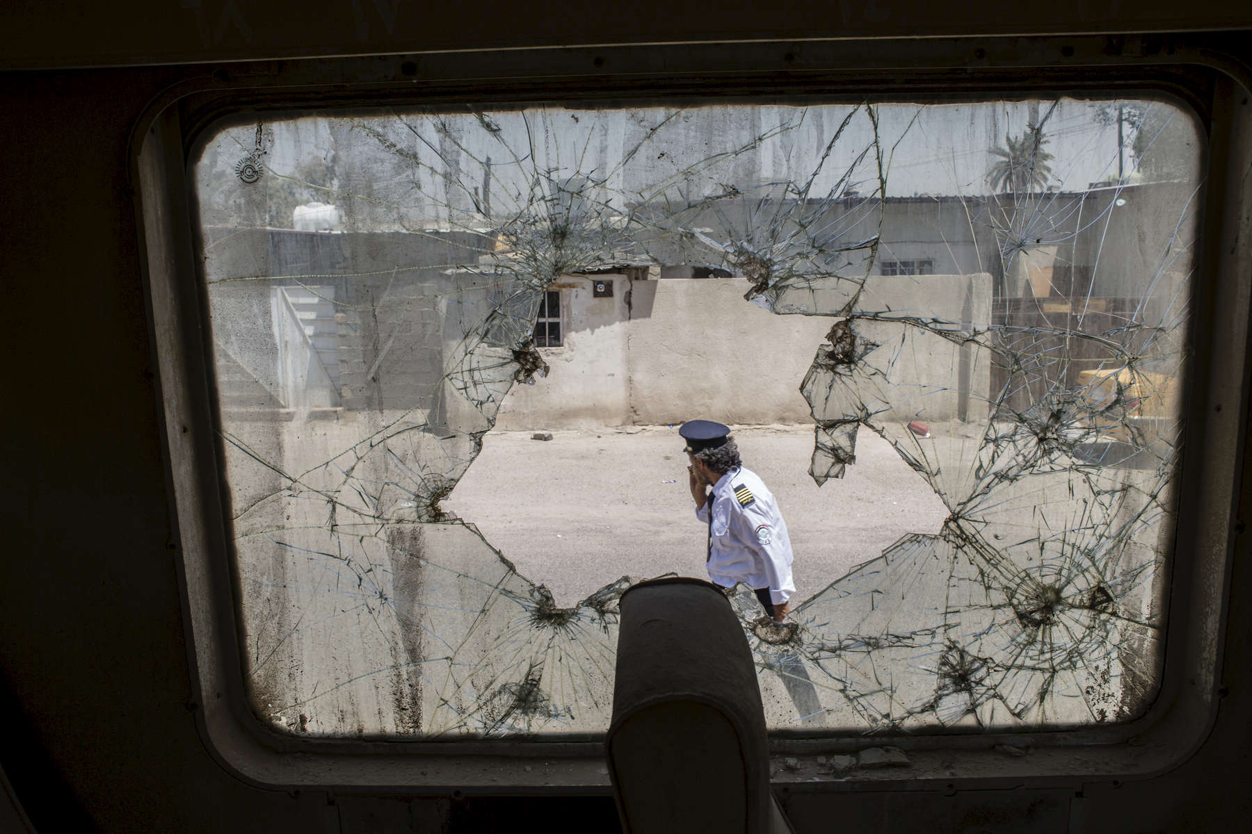 11/08/2016 -- Baghdad, Iraq -- Al-Karkhi walks past a train that was hit during crossfire between the US-led coalition and Iraqi forces in 2003. Bullet holes are seen across the window and carriage itself.