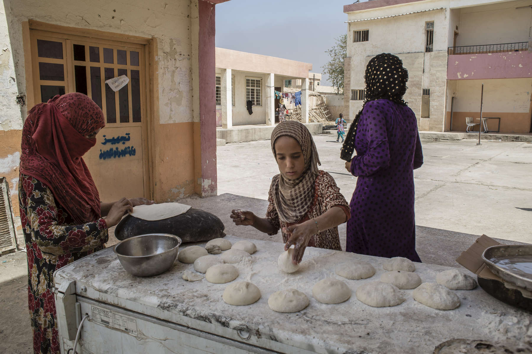 02/09/2016 -- Haji Ali Village, Iraq -- Iraqi women bake bread in a makeshift displacement camp in a school in Haji Ali. The UN warns that the humanitarian response to Iraq's displacement crisis is severely underfunded