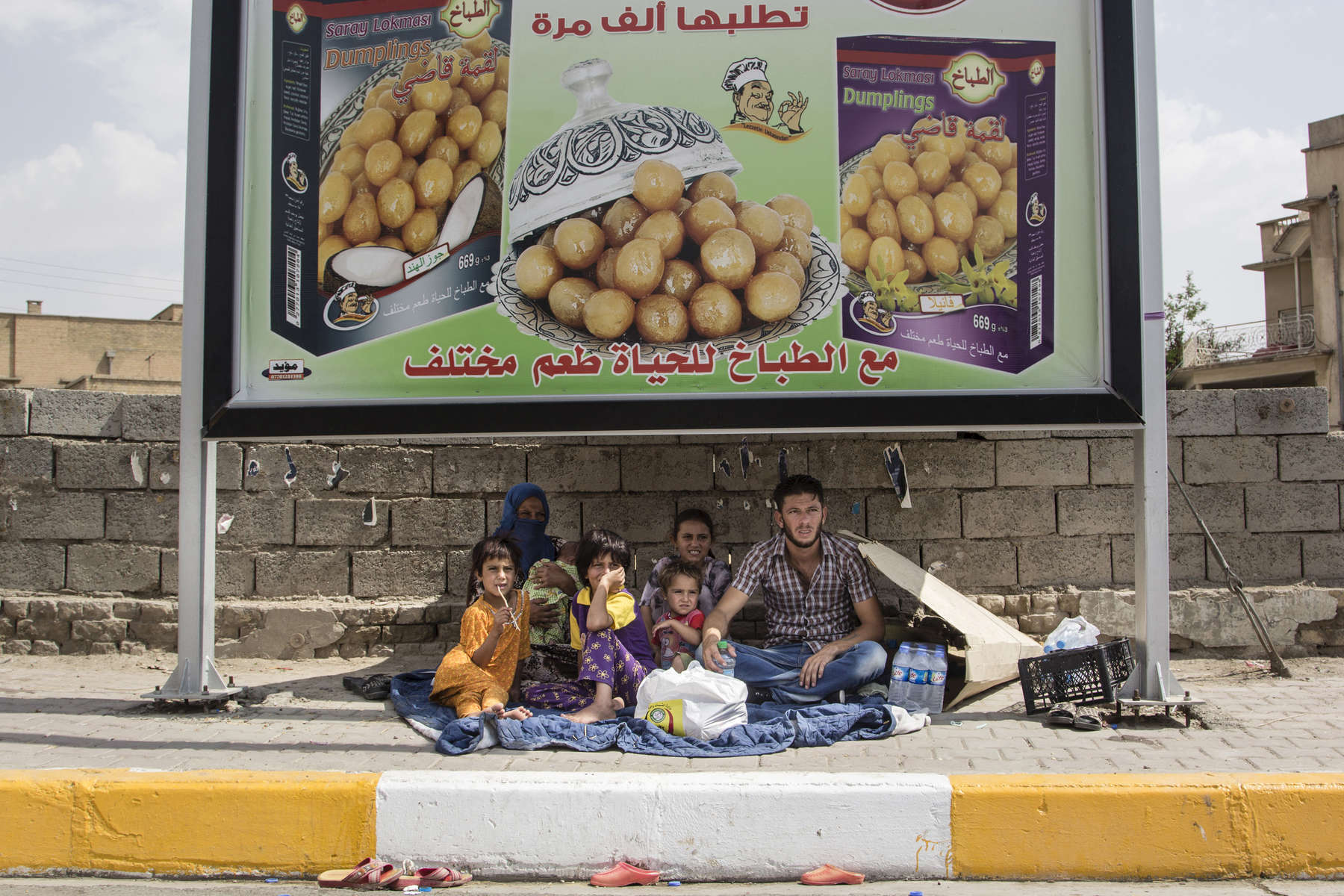 22/07/2014. Kirkuk, Iraq. A Sunni refugee family from Mosul shelter underneath a hoarding advertising sweets in Kirkuk, Iraq. The family left all of their possessions behind in Mosul when they fled to escape bombing by the Iraqi Air Force.