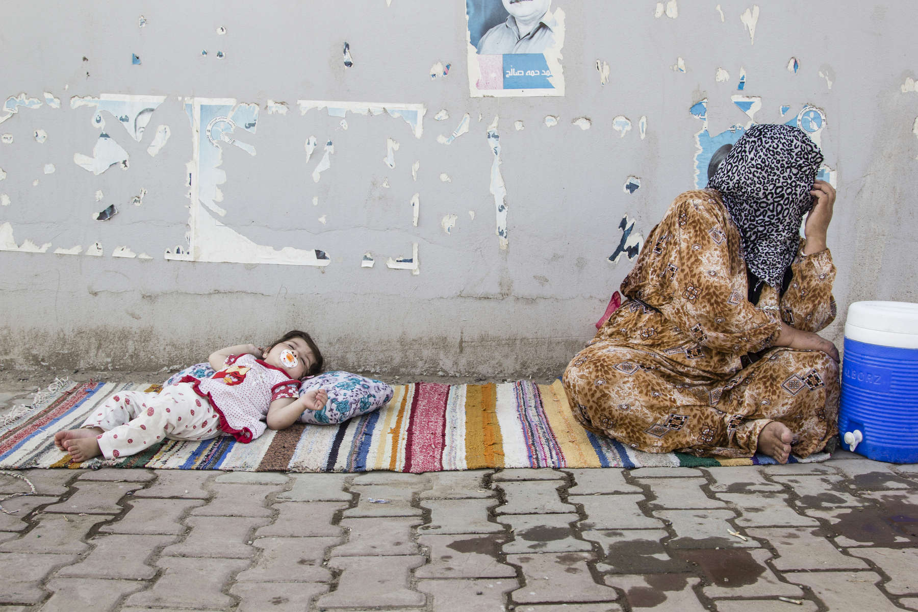 24/07/2014. Kirkuk, Iraq. An Iraqi Arab refugee from Mosul and her daughter are seen on the streets of Kirkuk, Iraq.