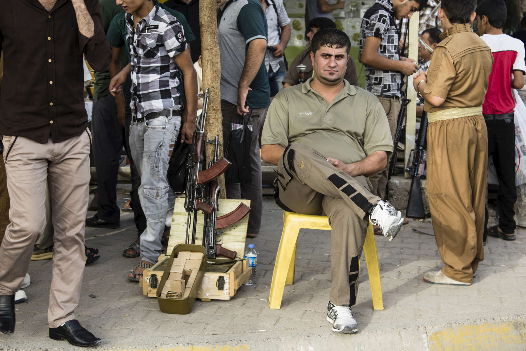 25/07/2014. Kirkuk, Iraq. A gun seller sits next to two Kalashnikov (AKMS) assault rifles in the Gun Market of the Kirkuk Bazaar, Iraq. Guns sellers don't sell guns to Arab people, because they consider them as an enemy.