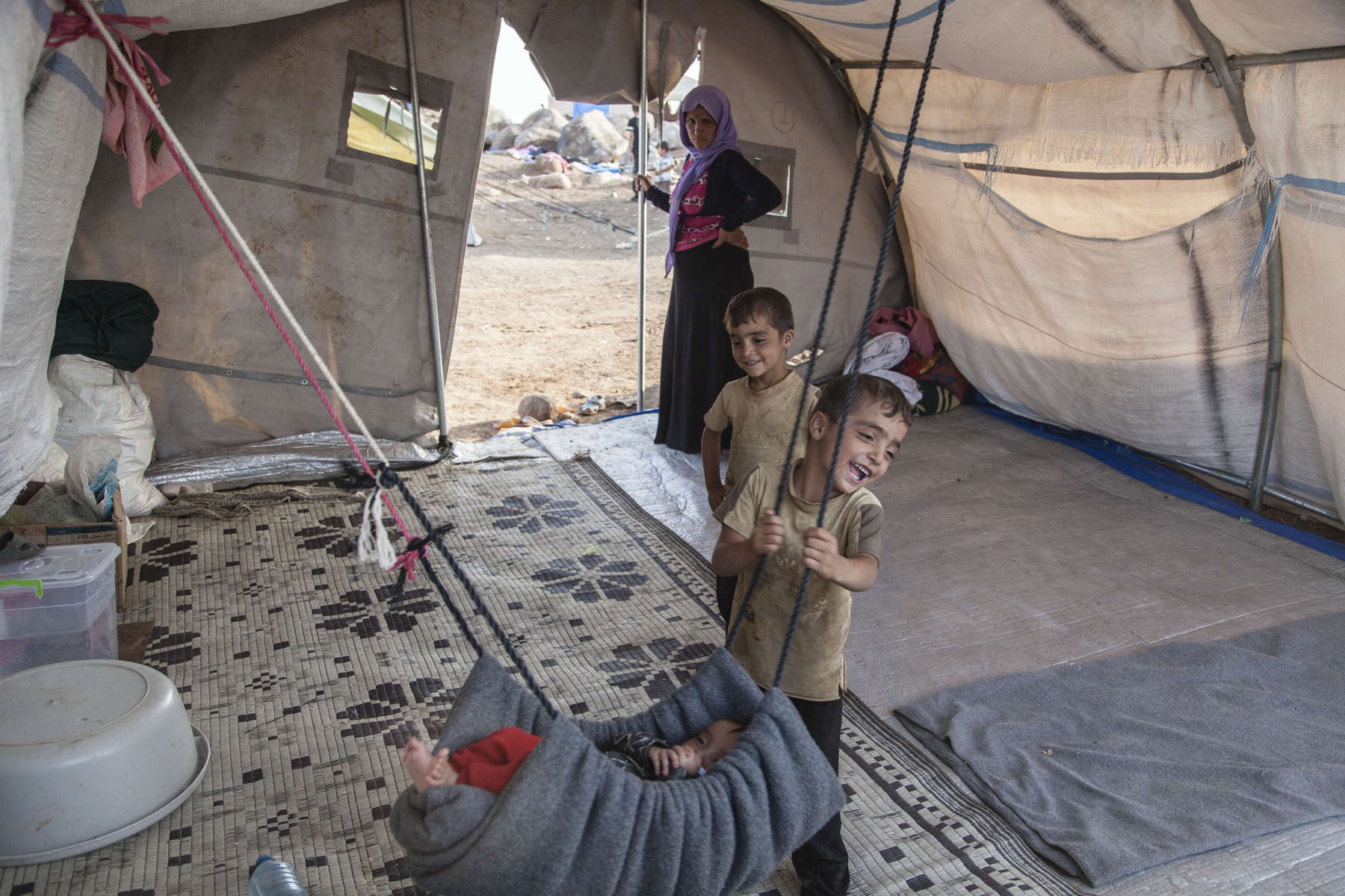 13/08/2014 -- Newroz Camp, Dirk, Syria -- Shero 8 y.o. plays with his brother inside their tent at Newroz camp. They were stranded on Sinjar mountain for six days and had reached the camp on the 11th of August.