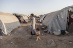 13/08/2014 -- Newroz Camp, Dirk, Syria -- A young Yazidi woman and a toddler walks by inside the camp of Newroz.