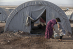 13/08/2014 -- Newroz Camp, Dirk, Syria -- A Yazidi woman is helped by her daughter to clean the entrance to their tent in camp Newroz.
