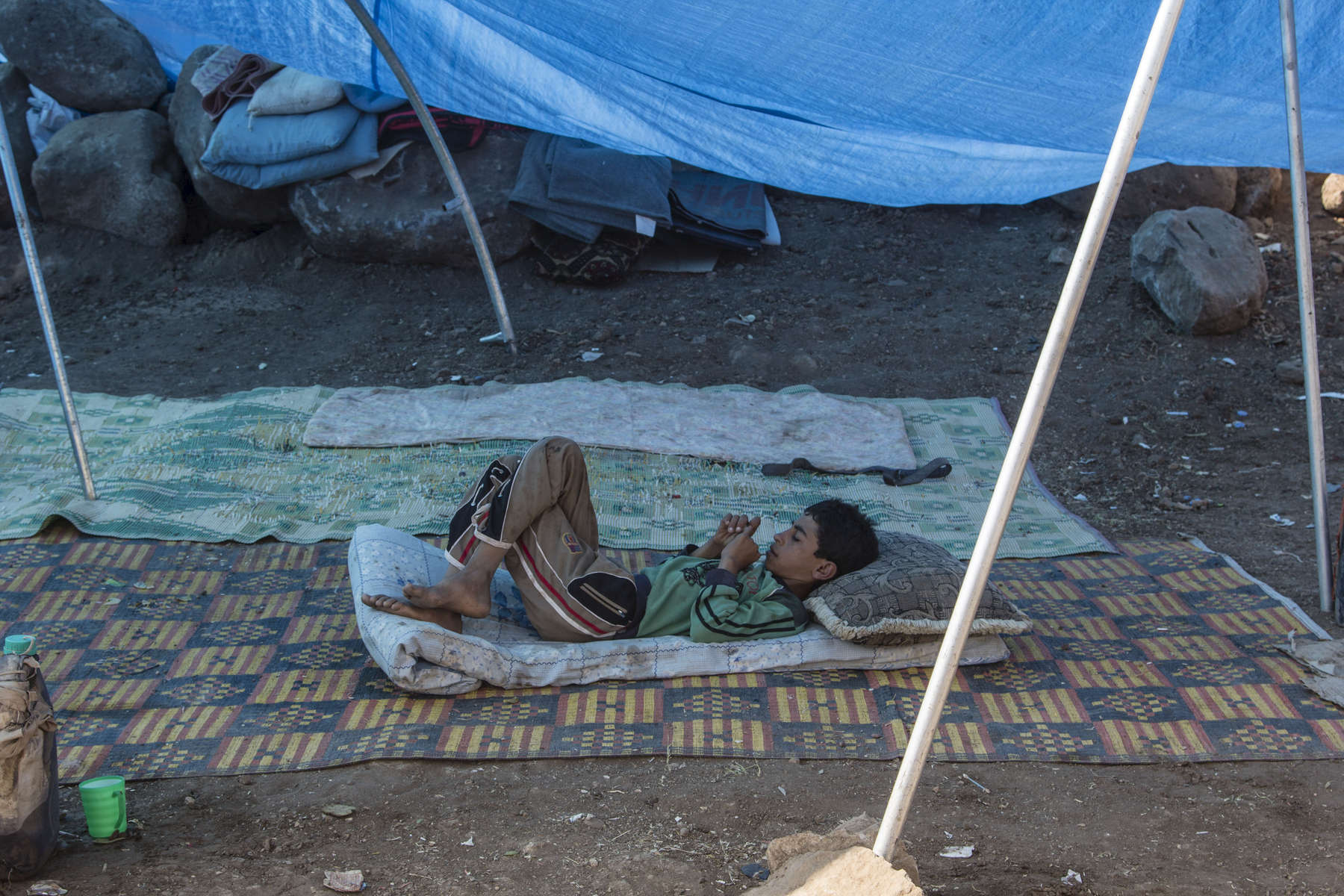 14/08/2014 -- Newroz Camp, Dirk, Syria -- A young Yazidi boy rests in the shade of a tent after arriving at Newroz camp.