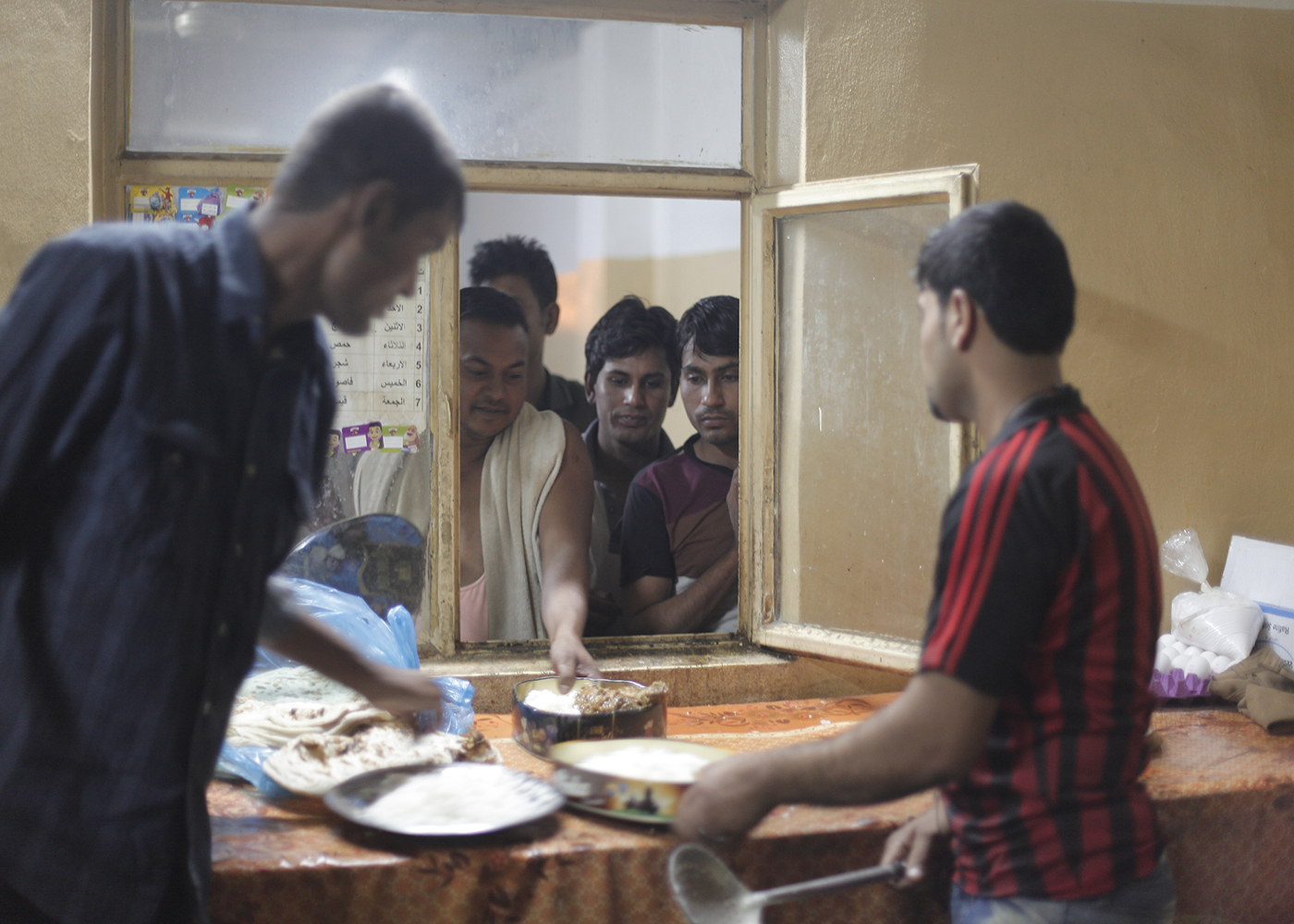 10/10/2014 -- Kirkuk, Iraq -- Bangladeshi workers get dinner in the garage where they live on Kornish street.