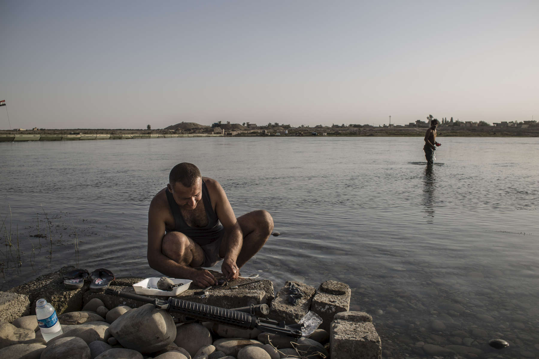 02/09/2016 -- Qayarah, Iraq --  An Iraqi soldier cleans his rifle in the Tigris river near Qayyarah.
