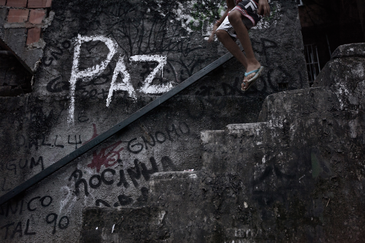 A youth jumps down a stairway with the word {quote}peace{quote} written on the wall, in the Shantytown of Rocinha, the biggest slum of Rio de Janeiro, Brazil, February 22, 2012.Initiated in 2008, the UPP, short for Unidade de Polícia Pacificadora (in English, Pacifier Police Unit or Police Pacification Unit), is a new system of community policing in Rio de Janeiro's favelas once run by drug traffickers. While many believe that UPPs have helped quell violence by opening the doors of the favelas to public services such as legal electricity supply, garbage collection, education, public works and social assistance program, others see the pacification program as a temporary cover-up to security problems in Rio de Janeiro.