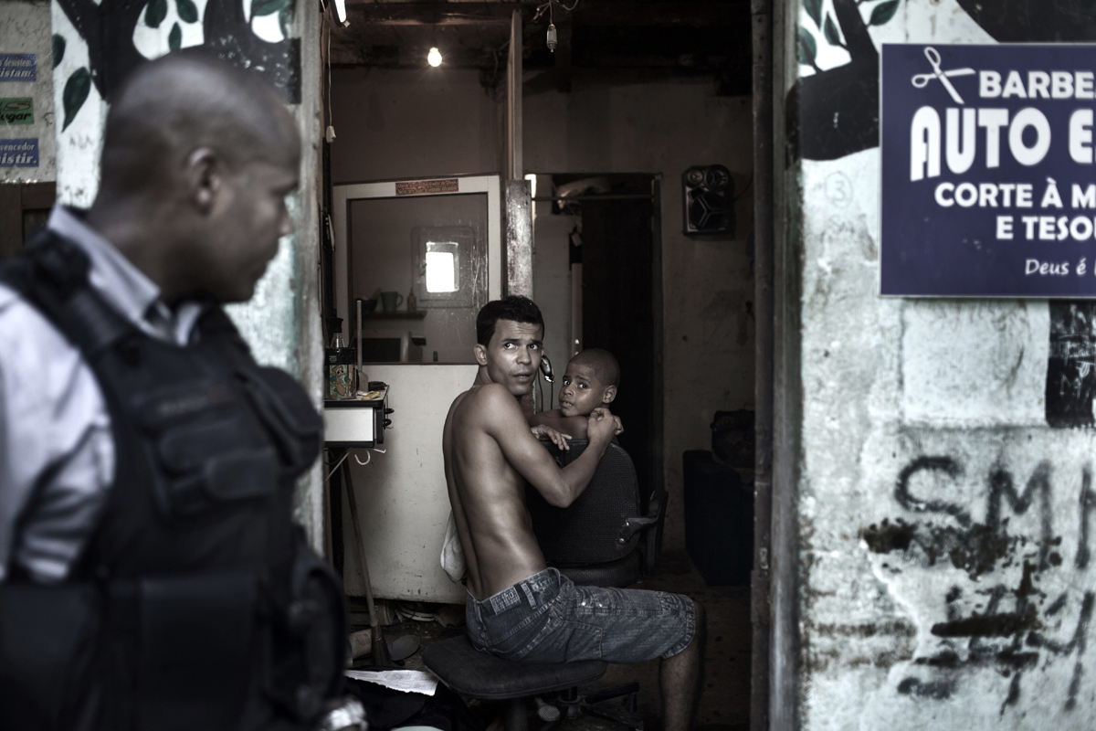 UPP soldier Franca, walks in front of a barber shop while its owner gives a haircut to a client, in the Shantytown of Sao Carlos, in Rio de Janeiro, Brazil, March 15, 2012.