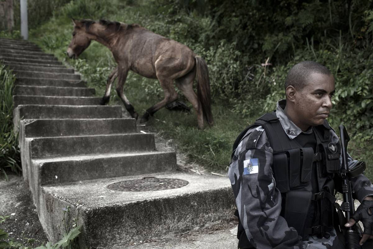 A horse runs away from a Riot Police officer, while he patrols during the Occupation of one shantytown who belongs to the group of slums called Complexo de Alemao, in Rio de Janeiro, Brazil, April 26, 2012.Initiated in 2008, the UPP, short for Unidade de Polícia Pacificadora (in English, Pacifier Police Unit or Police Pacification Unit), is a new system of community policing in Rio de Janeiro's favelas once run by drug traffickers. While many believe that UPPs have helped quell violence by opening the doors of the favelas to public services such as legal electricity supply, garbage collection, education, public works and social assistance program, others see the pacification program as a temporary cover-up to security problems in Rio de Janeiro.