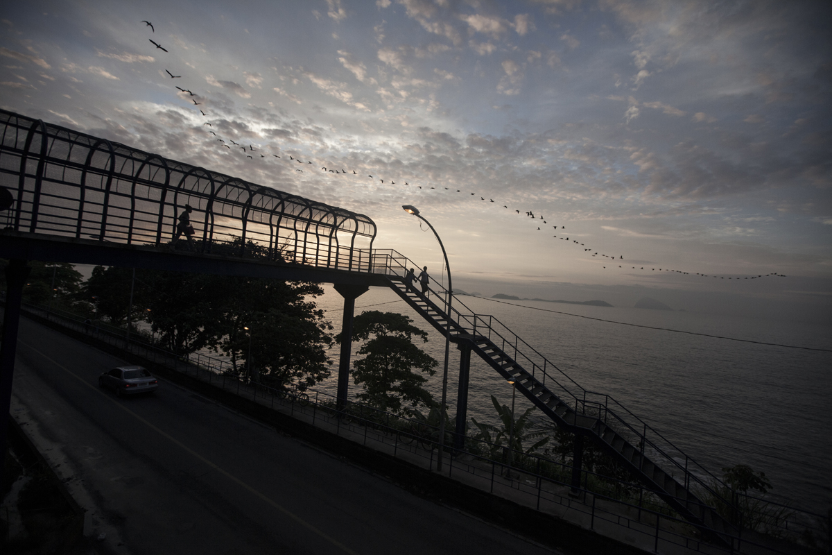 Residents of the shantytown of Vidigal crossing a bridge over the road of Niemeier on their way to work in Rio de Janeiro, Brazil, February 13, 2012. Initiated in 2008, the UPP, short for Unidade de Polícia Pacificadora (in English, Pacifier Police Unit or Police Pacification Unit), is a new system of community policing in Rio de Janeiro's favelas once run by drug traffickers. While many believe that UPPs have helped quell violence by opening the doors of the favelas to public services such as legal electricity supply, garbage collection, education, public works and social assistance program, others see the pacification program as a temporary cover-up to security problems in Rio de Janeiro.