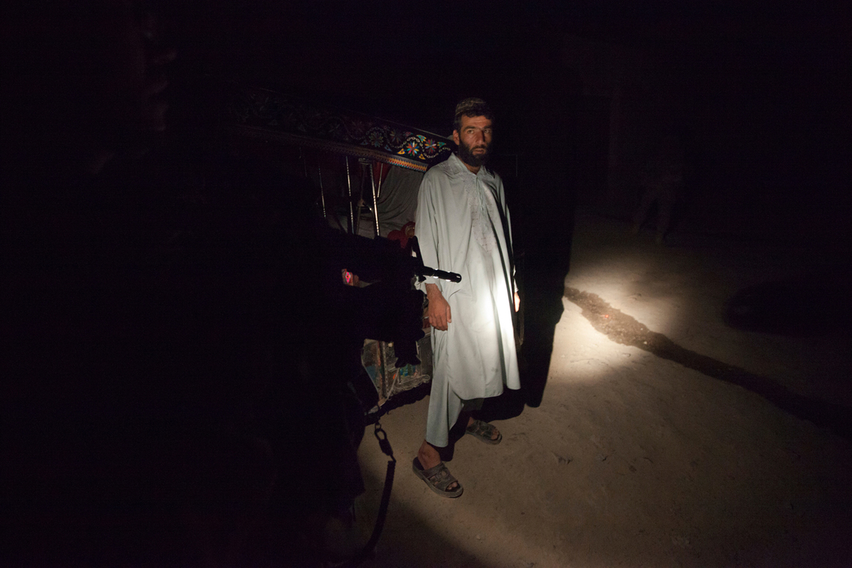 A soldier from the 2nd Platoon of the 561st Military Police Company in Kandahar, shines his flashlight towards an Afghan civilian while on a routine patrol in Kandahar, Afghanistan, October 02, 2011.