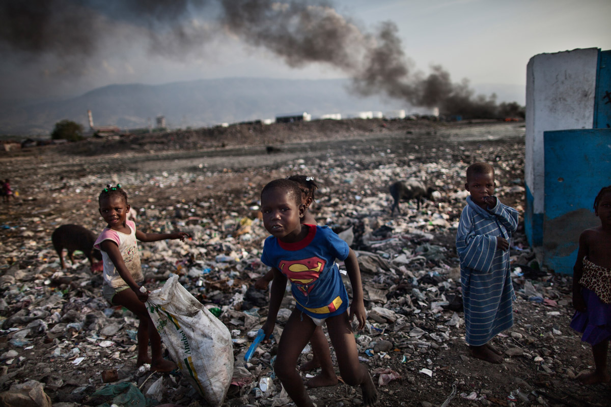 A group of children collecting garbage at a garbage dump in  Port-au-Prince, Haiti, April 02, 2012.At the base of Port-au-Prince´s hilly terrain, Cite Soleil has inadvertently become a collection point for much of the city´s trash, which washes down to the neighborhood with each rain storm. The life expectancy in the slum is dramatically low as there is sparse access to sanitation and health services.