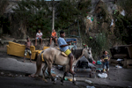 A teenager rides a horse down the street in the Complexo do Penha,behind him, some of his friends spend the afternoon playing with kites, in Rio de Janeiro, Brazil