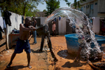 A man throws a bucket of dirty water before having a shower in the refugee camp of the State of Acre, in Brasileia, Brazil, September 28th, 2013.