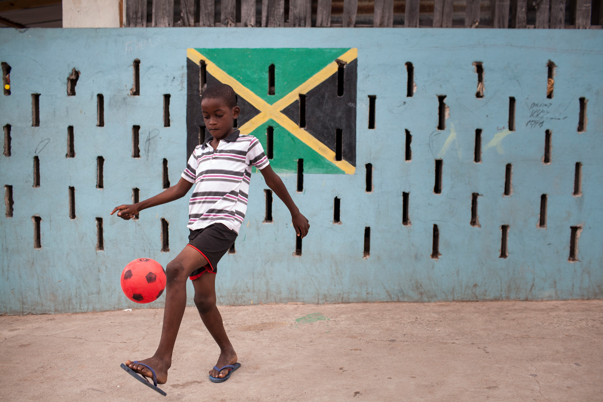 Kid playing Soccer in the neighborhood of Trenchtown, in Kingston, Jamaica