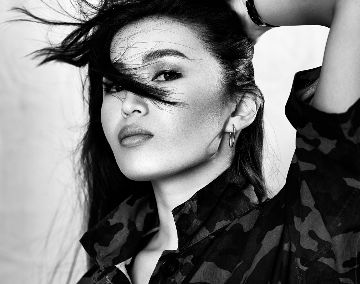 Model wearing an army jump suit for this fashion black and white image