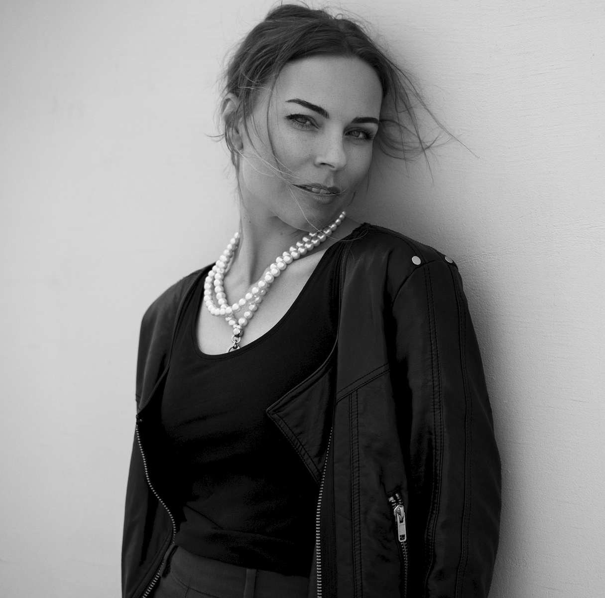 A black and white fashion image of model Ingvill posing against a wall wearing a black jacket and white pearls necklace
