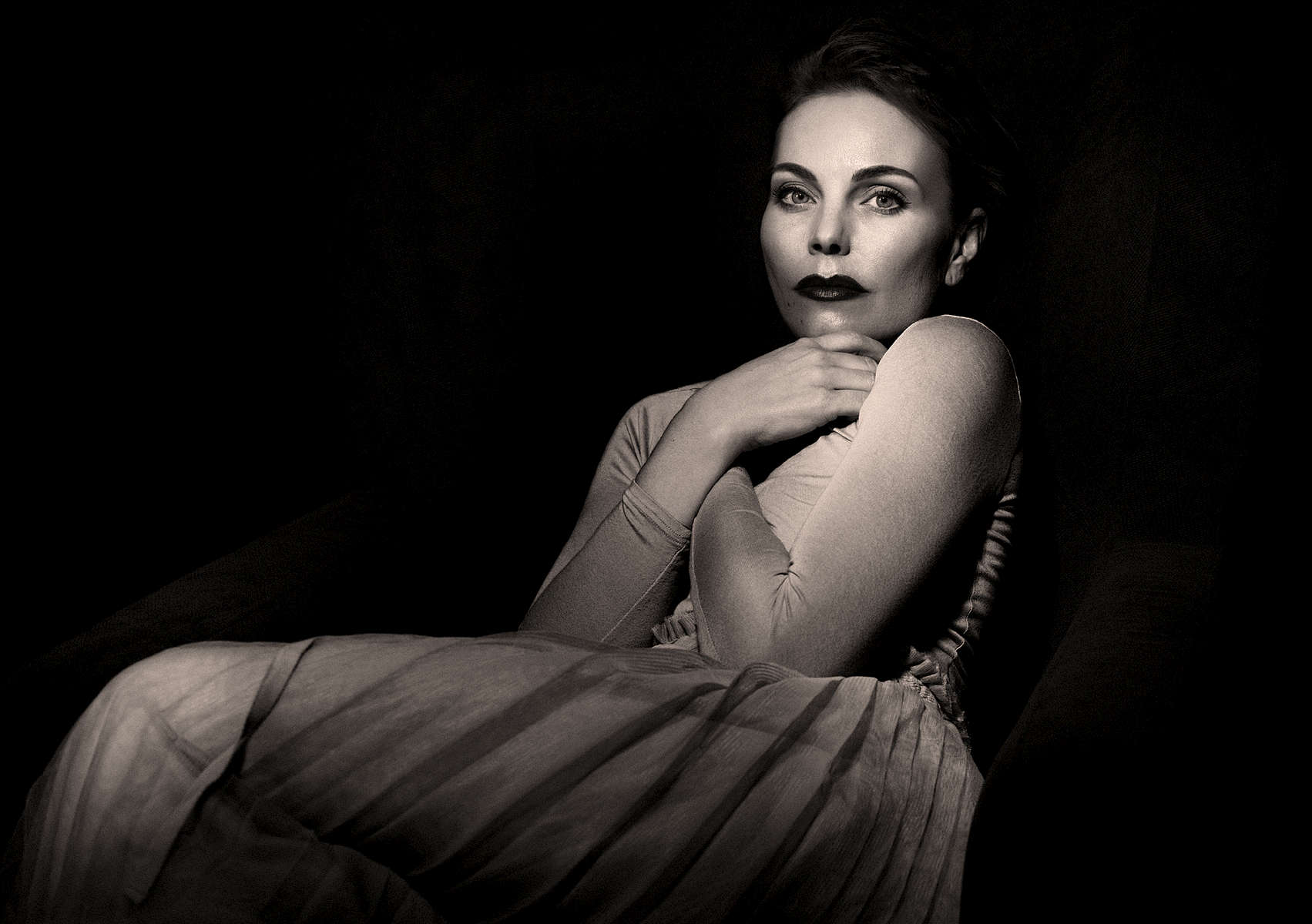 My wife, amazing and very beautiful model sitting on a chair creating this black and white film noir styled image.