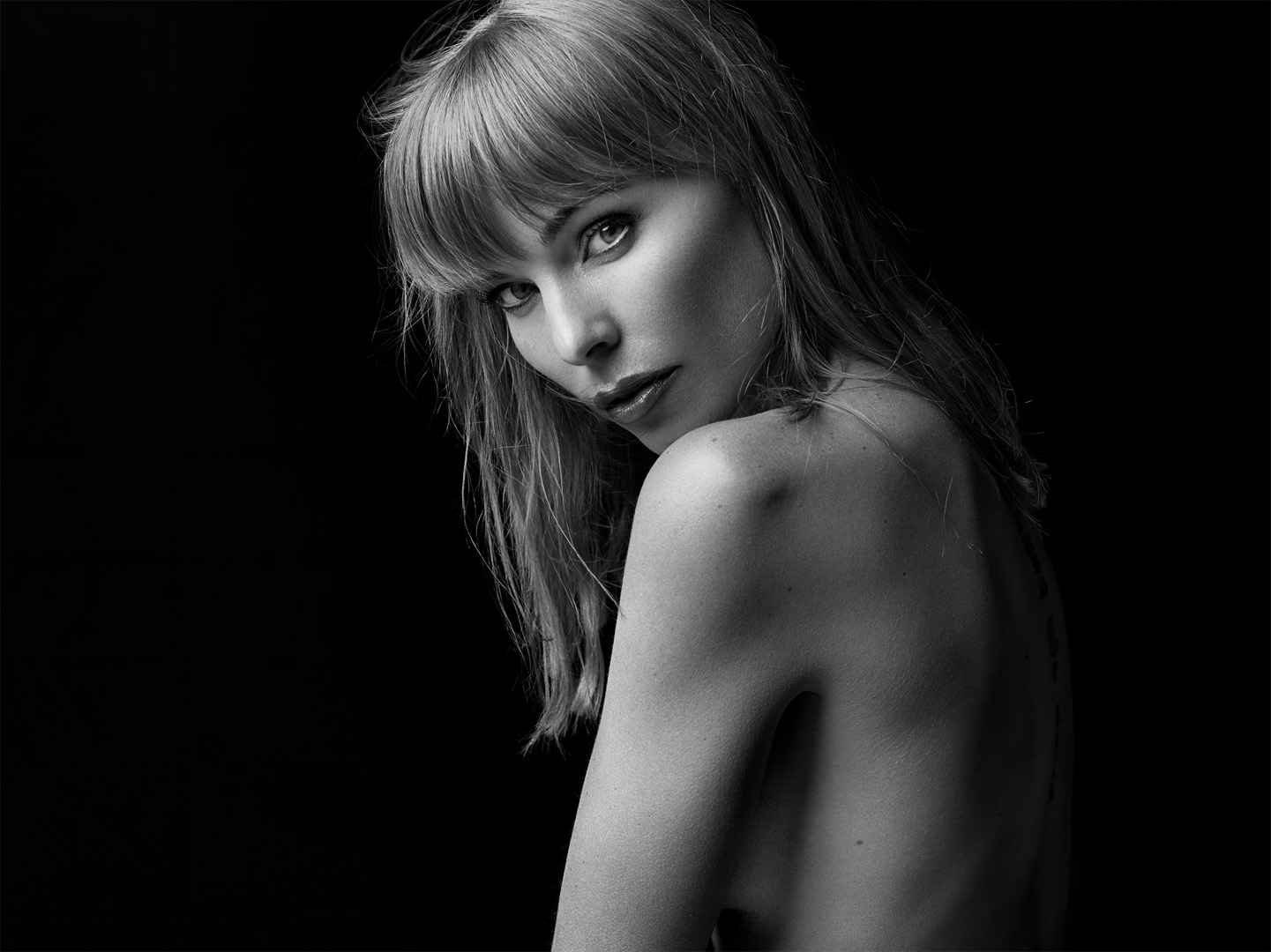 In this black and white image, model Ingvill is posing with her back and left shoulder towards the camera