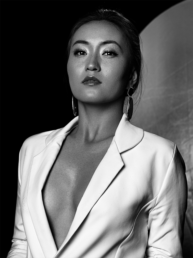 Model posing in a white suit jacket in this mid-shot black and white image