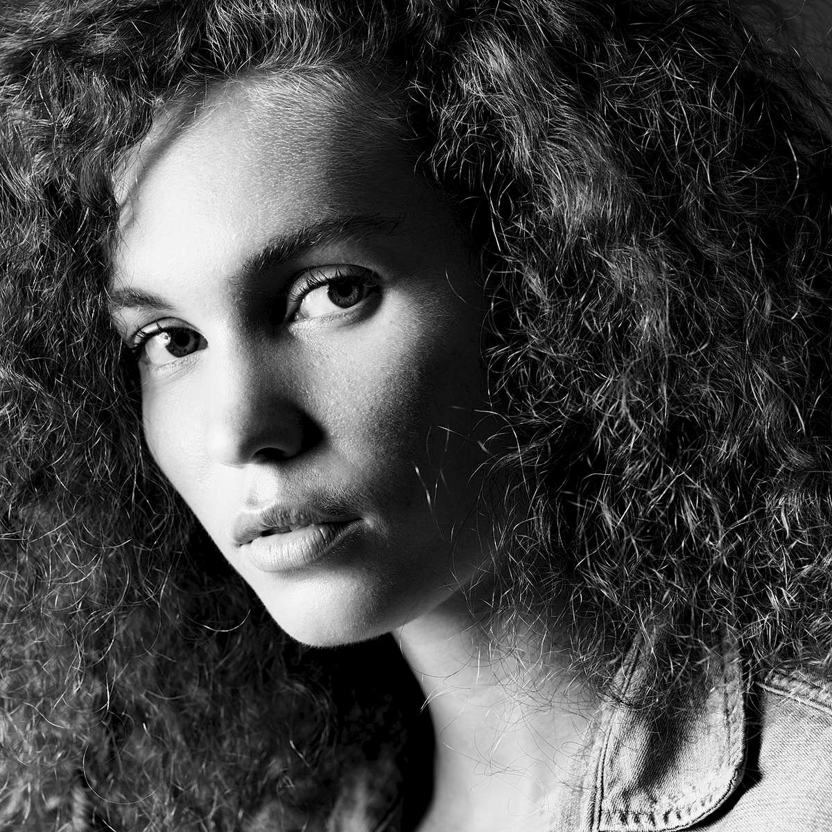 A portrait headshot of model Sophie captured as a black and white image