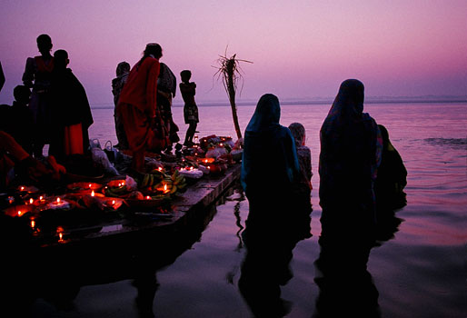 At sunset Hindu women pray in the Ganges River. As part of their prayers, they cast small candles in the river. Varanasi, India 1997