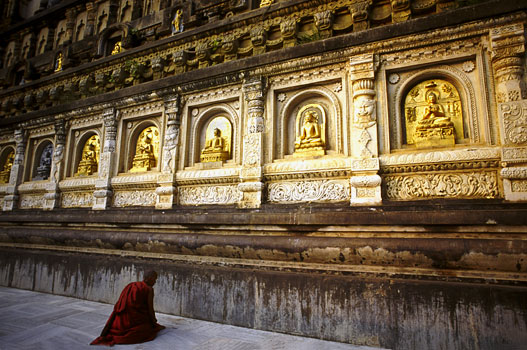 A Buddhist monk prostrates before images of the Buddha lining the Mahabodi Temple. This temple was built in the 3rd century BC by Emperor Ashoka to commemorate the Buddha and his place of enlightentment.Bodhgaya, India 1997