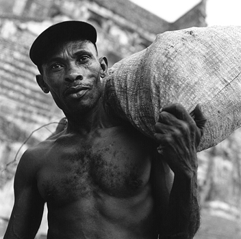 A man carries a bag of roots and plants that he has gathered on a nearby mountain. Milot, Haiti, 2004