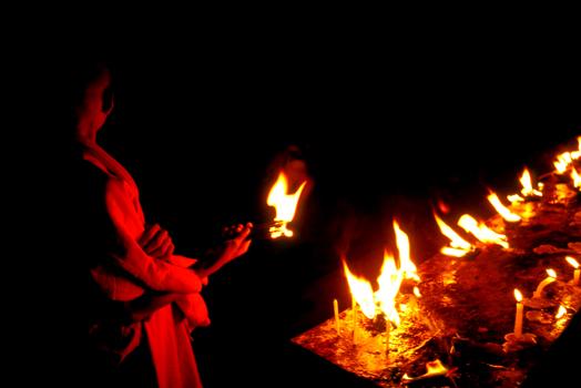 A Buddhist nun burning incense for a prayer near the Mahabodhi Temple. Bodhgaya, India 1997