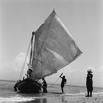 Children play on a fishing boat after it arrives back from a day at sea. Cap-Haitien, Haiti 2004