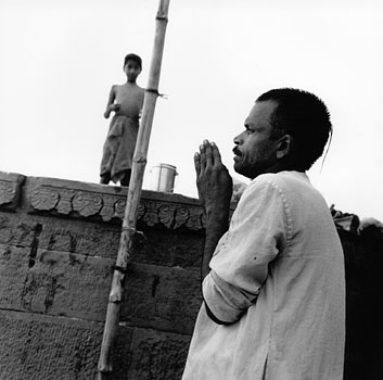 A Hindu man does his daily prayers atop one of the 100 ghats that line the west bank of the Ganges Rver.Varanasi, India 1997