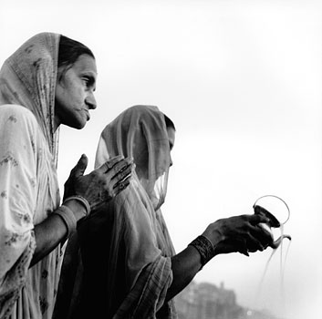 Wading into the waters of the Ganges River, two Hindu women pray at sunrise. Varanasi, India 1997