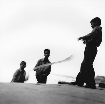 Three young boys play with a piece of cloth on the ghats (bodies of steps) that lead down to the Ganges River. Varanasi, India 1997