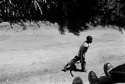 A young boy walks along side a taptap (or taxi) as it travels the main road in the north from the Dominican Republic. Many roads in Haiti are unpaved and peppered with huge pot holes making travel slow and dusty. Ouanaminthe, Haiti 2004