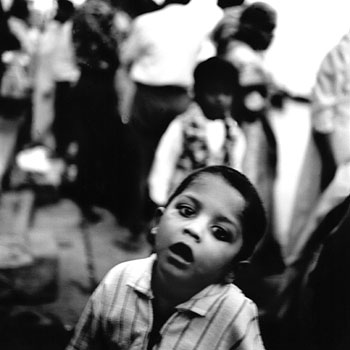 A young Hindu boy wanders along the ghats that lead to the Ganges River. Varanasi, India 1997
