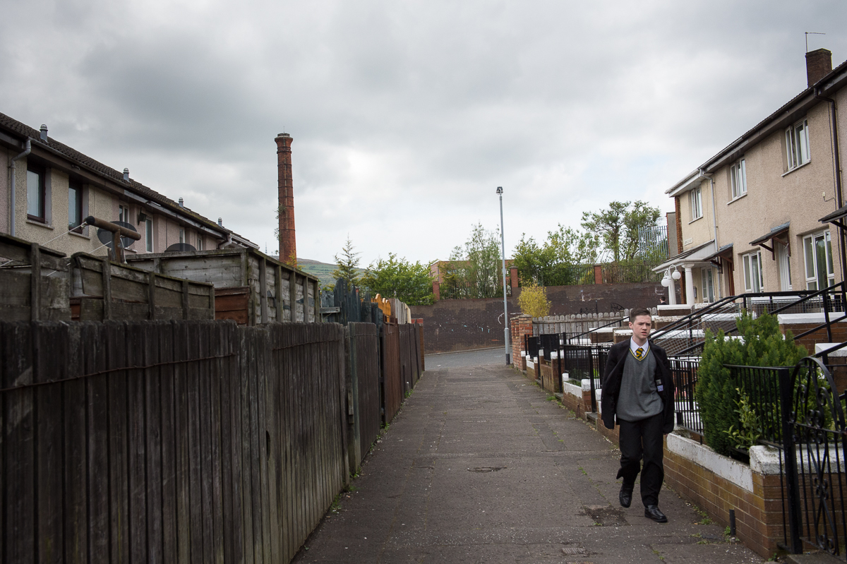 After school a teenager walks in an alley in the Catholic Ardoyne area of north Belfast.Education is highly segregated with 95 percent of children attending single-identity schools. Most of the schools have their own distinct uniform and since schools are overwhelmingly either Protestant or Catholic, the school uniforms clearly identify a young person's community background.