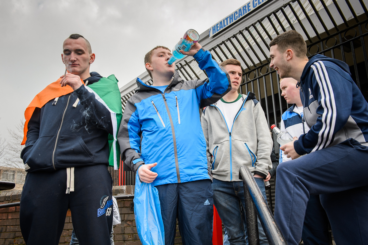 Young people celebrate Saint Patrick's day, in the Catholic Ardoyne area of north Belfast. The young man on the left has a tricolor flag, the national flag of the Republican of Ireland, draped around him.