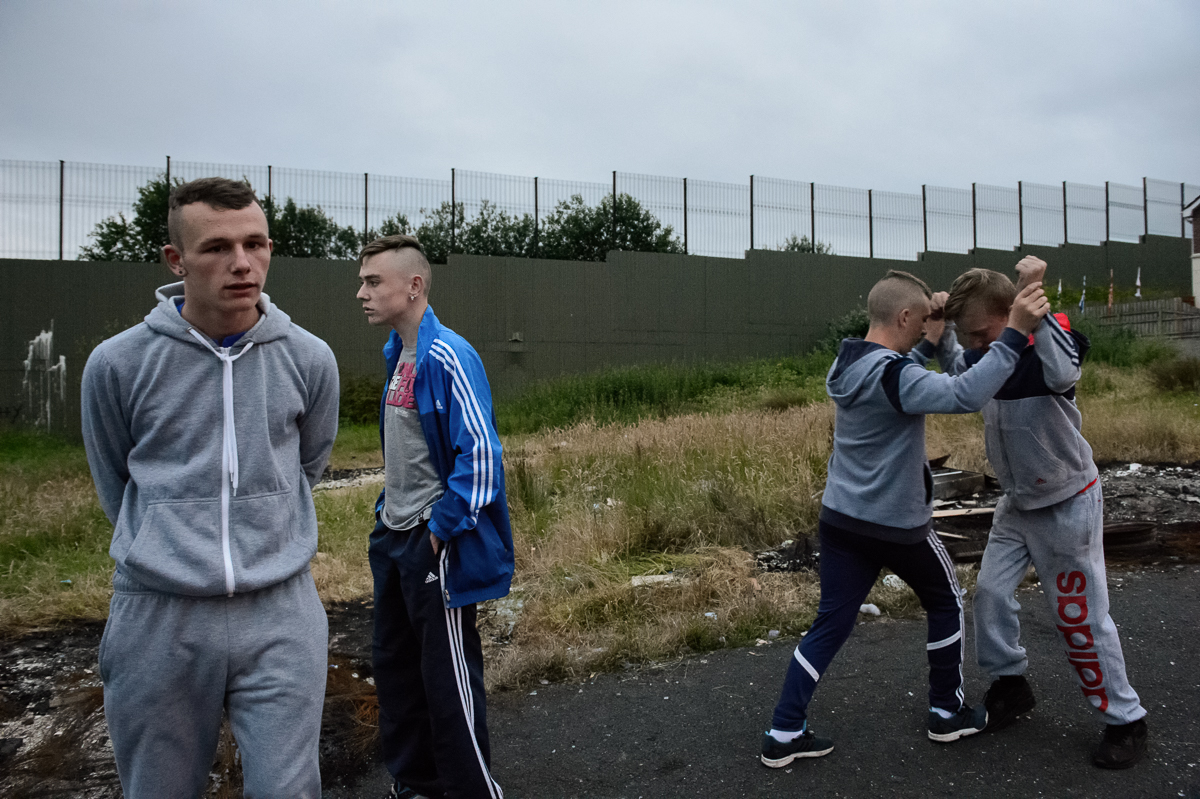 Young people near a so-called peace wall in north Belfast separating the Protestant Glenbryn area from the Catholic Ardoyne area on the other side. {quote}Taking peace walls away is not going to take bitterness away{quote} said Michael (left), 19. {quote}The walls prevent a clash, the bitterness bounds off on them. They shouldn't come down over the next 100 years, there's still too much pain. Belfast is still totally a divided city.{quote}First built in 1969 as a temporary solution to reduce violence, the peace walls — a euphemism for segregation barriers — have increased in number and scale since the start of the peace process. The barriers take many forms: Not only walls but also fences, gates, roads and empty buffer zones divide the Catholic and Protestant communities in some of the city's most economically deprived areas. The government promised to take the barriers down by 2023, but many residents are not ready for them to come down any time soon. Not all interface areas — the common boundary between a Protestant and a Catholic area —  have a physical border. Sometimes there is only an invisible dividing line that local people are aware of.