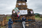 A young man wearing a uniform shirt of the Pride of Ardoyne Flute Band  — one of the many loyalist bands in Belfast, some of which are linked to paramilitary groups — adds an election poster of a Sinn Féin politician to a finished bonfire in the Protestant Glenbryn area of north Belfast. Other hated symbols on the bonfire are a banner referring to the IRA and signs protesting  restrictions on marching parades by the Parades Commission -an official bipartisan parade watchdog.Bonfires are traditionally lit in Protestant areas on the {quote}Eleventh Night{quote} of July to commemorate the victory of the Protestant William of Orange over his Catholic father-in-law King James II at the Battle of the Boyne in 1690. Preparations start months before with the collection of pallets and other materials like rubber tires. The bonfire is followed on July 12 by a large parade held by the Orange Order — a Protestant fraternal organization — and loyalist marching bands. The {quote}Twelfth{quote} as it is called is a tense period. Many Catholics consider the celebrations a display of sectarian triumphalism whereas for many working-class Protestants they are an essential expression of their cultural identity.