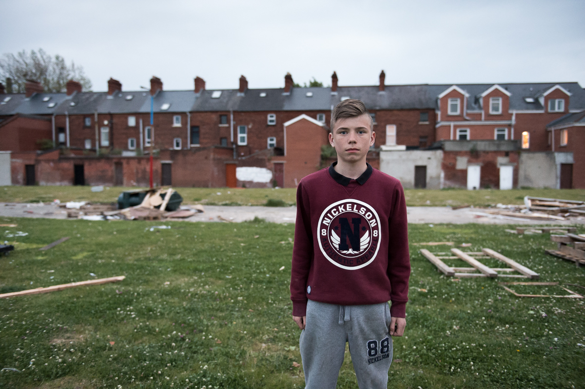 Ryan, 14, in the Village area of south Belfast. Behind him a lamp post in the colors red, blue and white of the Union Jack identifies the area as Protestant.  Flags, murals and painted curbs and lamp posts are common identity markers in Protestant working-class areas.Young working-class youth are growing up in a deeply divided society with an entrenched {quote}us and them{quote} mentality.